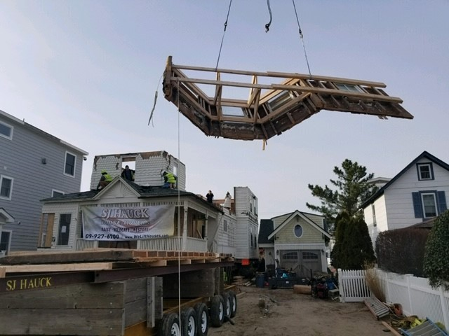 The house being delivered in sections off a flatbed truck